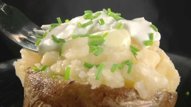 cu fork lifts a bite from steaming baked potato with sour cream and chives - kartoffelgericht stock-videos und b-roll-filmmaterial