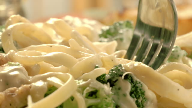 a fork lifts a bite of steaming chicken-broccoli pasta in alfredo sauce. - pasta video stock e b–roll