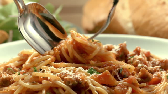 fork twirls spaghetti noodles into spoon from pasta marinara dish served on a plate