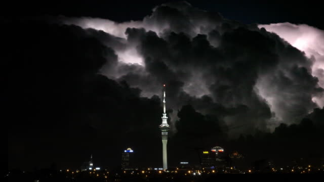 ws t/l forked lightning with storm clouds over cityscape / auckland, new zealand. - forked lightning stock videos and b-roll footage