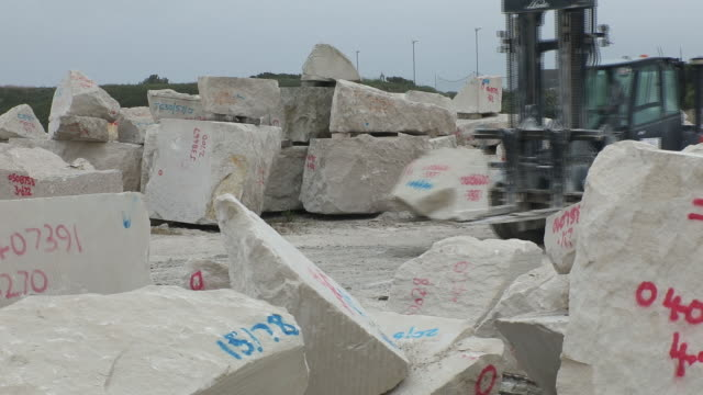 Forklift carrying block of limestone at Albion Stone exterior Portland Weymouth Dorset UK on Tuesday July 30 2019