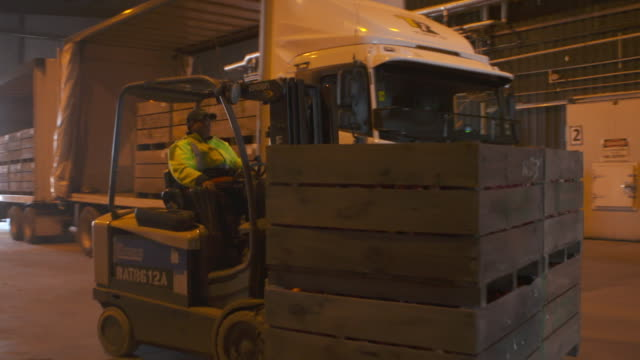 Forklift collecting crate from truck at onion processing warehouse and truck leaving plant