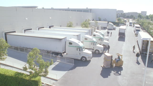 a forklift drives up a ramp into a warehouse as semi-trucks drive through a loading dock. - 2005 stock videos & royalty-free footage