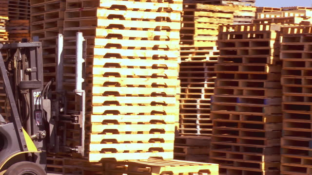 forklift grabs stack of new wood pallets and loads them on to flatbed truck for shipping  / Fontana, California, USA