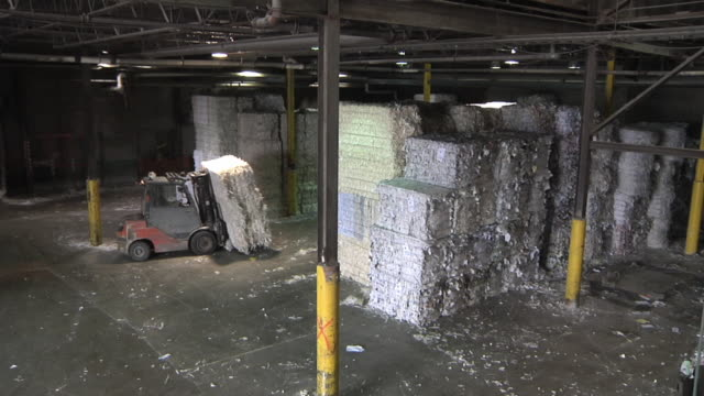 WS Forklift operator moves bales of recycled paper in paper mill / Manistique, Michigan, USA
