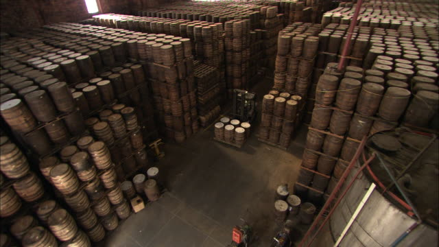 a forklift operator moves rum barrels out of a warehouse. - rum stock videos and b-roll footage