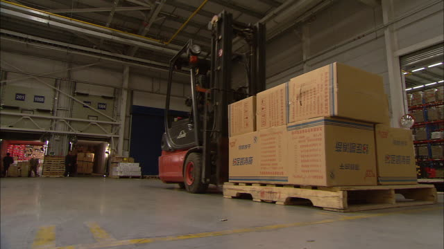 a forklift operator picks up a pallet of boxes and moves them to a truck positioned in the loading dock. - forklift truck stock videos and b-roll footage