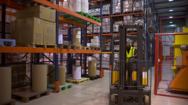 forklift pulling pallet of chemicals off a warehouse shelf - forklift stock videos & royalty-free footage