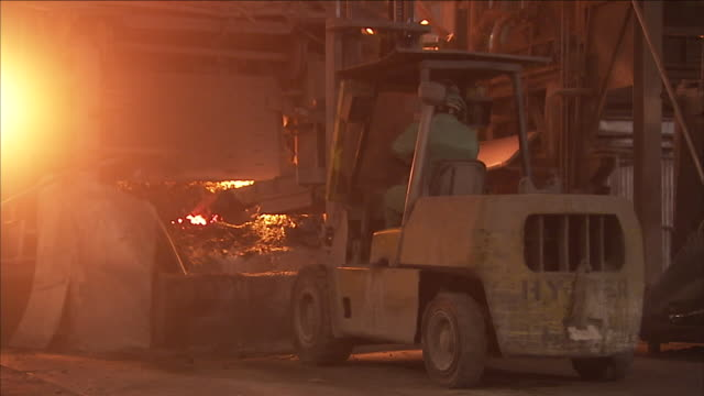 a forklift pushes materials into a steel factory furnace. - opificio video stock e b–roll