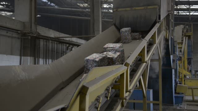 vídeos de stock e filmes b-roll de a forklift transports bales of crushed aluminum to a conveyer belt leading to a melting vat at the latasa reciclagem in pindamonhangaba state of sao... - cilindro veículo terrestre comercial