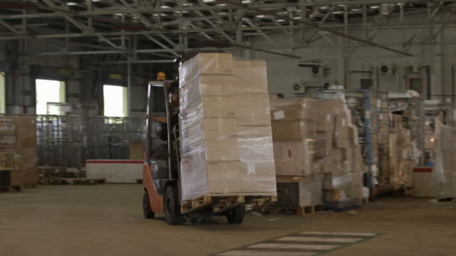 forklifts move packages around distribution warehouse - box container stock videos & royalty-free footage