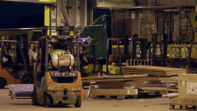 forklifts move packages around distribution warehouse - cardboard box stock videos & royalty-free footage