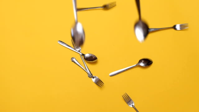 forks and spoons falling down - colored background stock videos & royalty-free footage