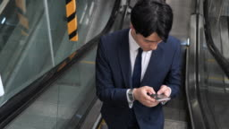 Formal Korean businessman commuting to work and using phone