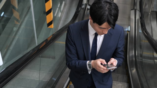 formal korean businessman commuting to work and using phone - stazione della metropolitana video stock e b–roll