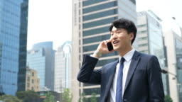 Formal Korean businessman using phone for communication with business partners