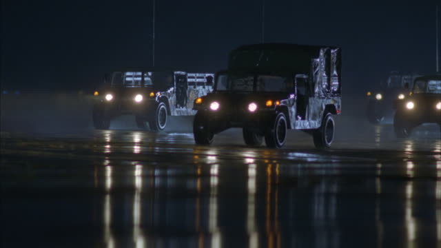 A formation of military jeeps, pickup trucks and vans is moving across an air force base tarmac.
