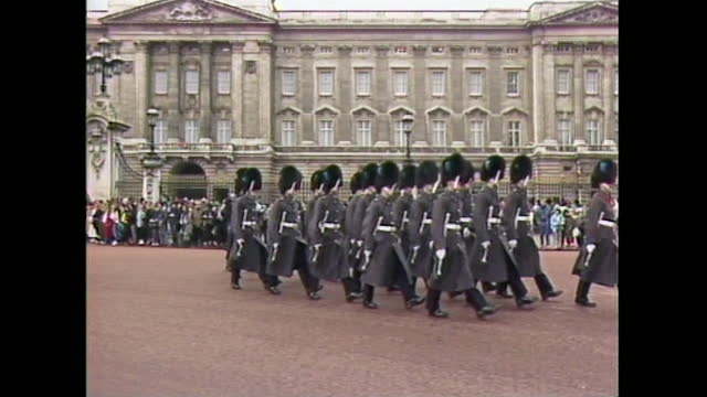 formation of soldiers marches outside buckingham palace as a crowd of spectators looks on, uk; 1988. - military uniform stock videos & royalty-free footage