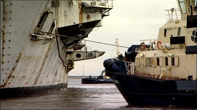 former aircraft carrier containing contaminated waste arrives in britain clemenceau in dock / various of tug boats towing former aircraft carrier... - nave da guerra video stock e b–roll