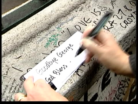former beatle george harrison: death announced; itn england: london: abbey road ext man writing message on wall outside recording studios where the... - george harrison stock videos & royalty-free footage