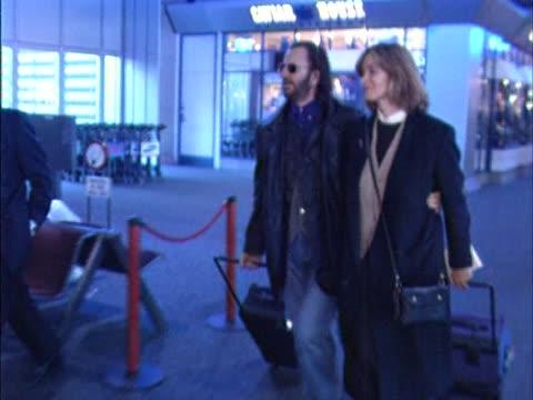 former beatle ringo starr strides briskly through heathrow with his wife actress barbara bach - ringo starr bildbanksvideor och videomaterial från bakom kulisserna