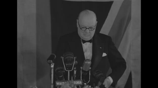 MCU Former British Prime Minister Winston Churchill wearing eyeglasses speaks into microphones with WALDORF ASTORIA plaque US British flags partially...