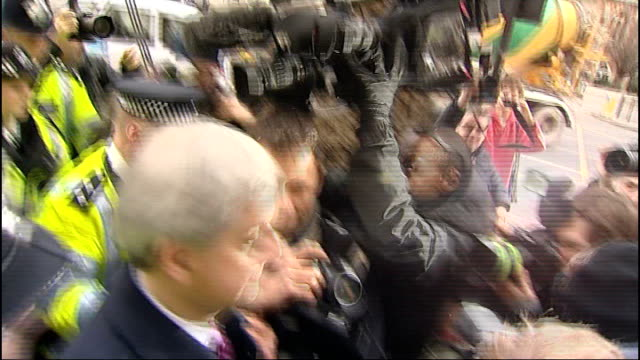 former energy secretary chris huhne and wife appear in court for speeding case; ext hunhe escorted by police officers through press scrum as leaving... - クリス ヒューン点の映像素材/bロール