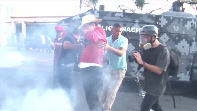 Former Honduran president Manuel Zelaya was the victim of rubber bullets and tear gas as he led a protest march against a contested presidential...