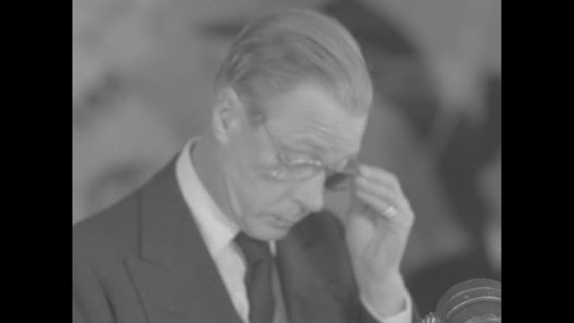 former king edward viii, duke of windsor, reads a short statement about his brother king george vi / wallis simpson, duchess of windsor stands at his... - エドワード8世点の映像素材/bロール