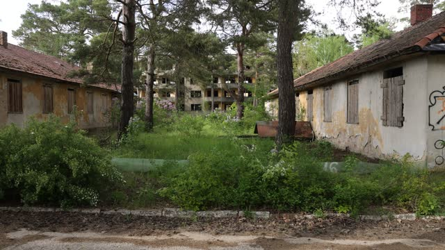 vidéos et rushes de former multistory soviet army barracks stands between original, abandoned houses for athletes marked with their housing complex names at the site of... - village