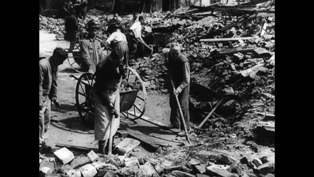 / former nazis forced to clear up bomb damage in their town / suited men with shovels. post war germany clean up on january 01, 1945 in germany - rebuilding stock videos & royalty-free footage