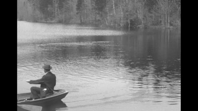 former president calvin coolidge works with his fishing line as he sits in a rowboat on the white river / another man rows the boat as coolidge casts... - coolidge calvin stock videos & royalty-free footage