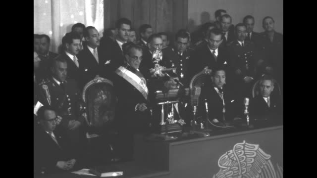 vidéos et rushes de former president miguel aleman seated on dais at the palace of fine arts listens as newly elected adolfo ruiz cortines makes speech / dignitaries... - président