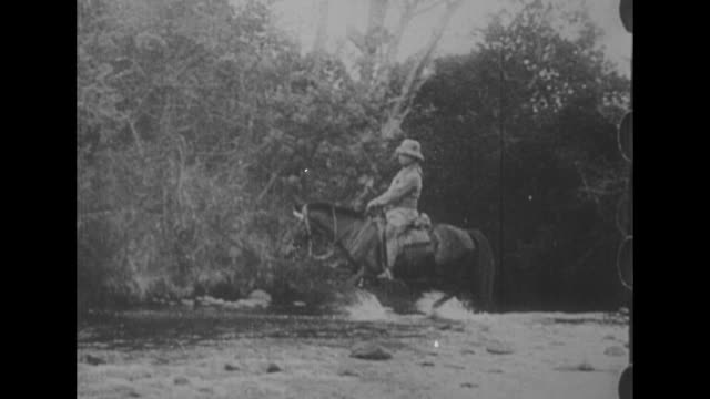 ws former president theodore roosevelt fords a river on horseback / roosevelt in safari hat watches as another man handles a hunting rifle other... - 1910 stock-videos und b-roll-filmmaterial
