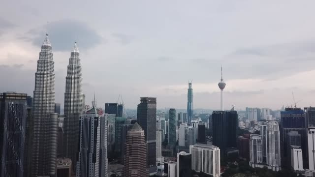 former prime minister najib razak sentenced to 12 years in jail; malaysia: kuala lumpur: ext drone footage of monorail along tracks and skyscrapers... - petronas twin towers stock videos & royalty-free footage