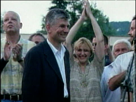 vídeos de stock, filmes e b-roll de former prime minister zoran djindjic (now deceased) raises arms in air and walks past cheering people towards podium after election results serbia; 2000 - prime minister