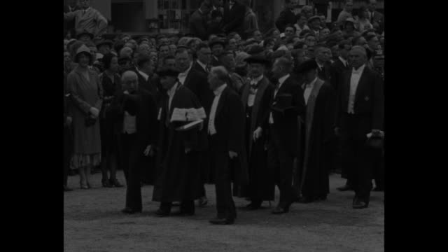 former us ambassador to germany jacob schurman wearing hat leads procession of dignitaries across square / wider view of procession / view of... - ハイデルベルク点の映像素材/bロール