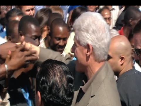 Former US President Bill Clinton and UN Secretary General Ban KiMoon shake hands with people during visit to Haiti 10 March 2009
