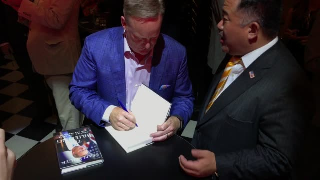 former white house press secretary sean spicer greets guests as he signs a copy of his new book 'the briefing politics the press and the president'... - former stock videos and b-roll footage