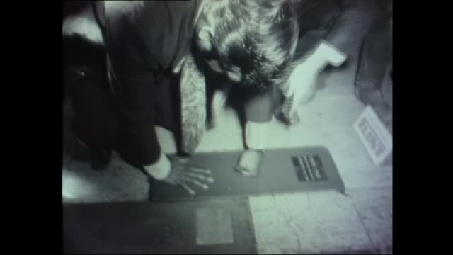 Former world bantamweight champion boxer Lionel Rose puts hand and fist imprint into concrete pavement in front of onlookers / Rose washes hands in...