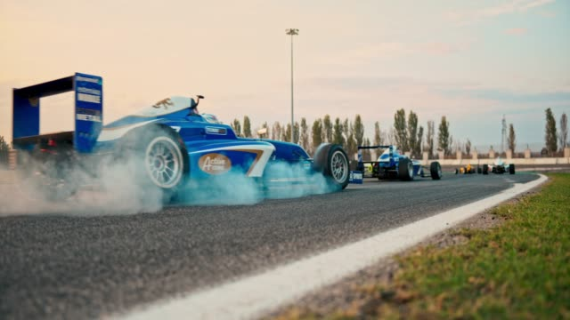 slo mo ld formula cars racing on the track and smoke rising from the tyres - focus on background stock videos & royalty-free footage