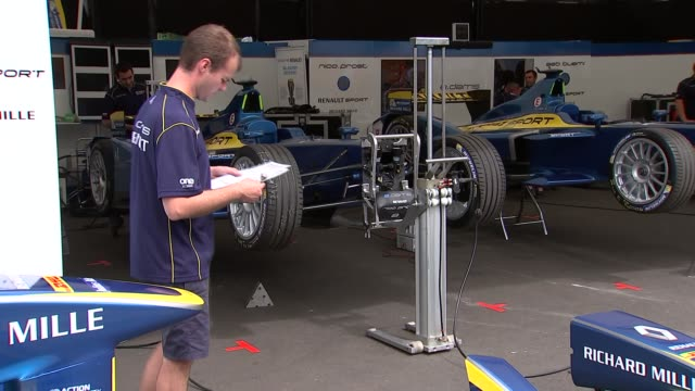 Formula E at Battersea and interviews Cars in garage area / mechanics working / car being lifted / 'Renault Nicolas Prost' tent / 'Sebastien Buemi'...