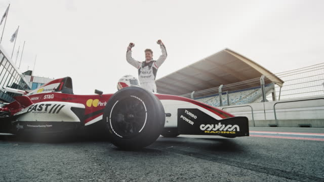 formula one driver cheering after victory on racetrack - automobilismo video stock e b–roll