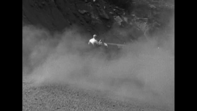 VS Formula One race cars on mountainous road / VS cars round hairpin curves on dirt road some sliding all raising clouds of dust / VS spectators line...