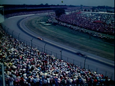formula one race cars speeding along indianapolis motor speedway competing in indy 500 race as viewed from crowded spectator stands / pit crew member... - 1972 stock videos and b-roll footage
