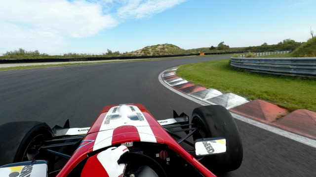 formula one racing car driving on a racetrack - velocità video stock e b–roll