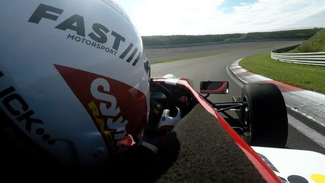 formula one racing car driving on a racetrack - casco da motociclista video stock e b–roll