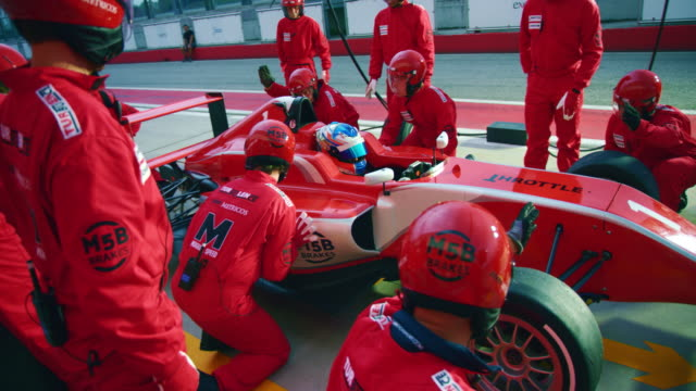 formula pit crew changing tyres on the car - athlet stock-videos und b-roll-filmmaterial