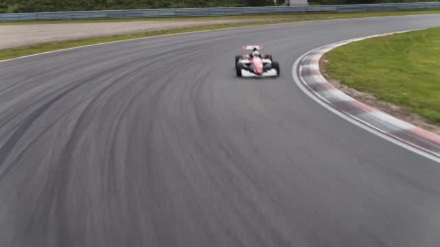 formular one racing car driving on a racetrack - automobile da corsa video stock e b–roll