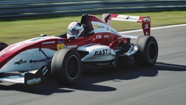 vídeos de stock e filmes b-roll de formular one racing car driving on a racetrack - desporto de competição desporto